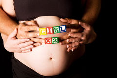 Pregnant couple holding wooden playing blocks. Pregnant couple with wood playing blocks indicating they expect twins Stock Photography
