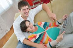 Pregnant couple at home using tablet computer Royalty Free Stock Photos