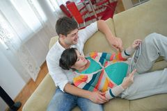 Pregnant couple at home using tablet computer Stock Photos
