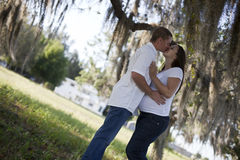 Pregnant couple kissing. A young man and pregnant woman kissing outside under a tree stock image