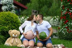 Pregnant couple kissing. funny pregnant girl with her husband play with watermelon and plush bear. Authentic lifestyle image royalty free stock photo