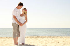 Pregnant couple in love on the beach Stock Image