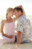 Pregnant couple in love on the beach Stock Photography