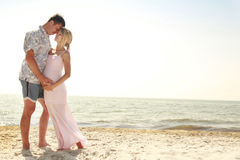 Pregnant couple in love on the beach Stock Photos