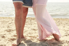 Pregnant couple in love feet on the beach Stock Photo