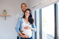 Pregnant couple loving. Happy african men embracing his pregnant girlfriend and looking at camera. Loving husband gently hugging pregnant wife at home Stock Photo