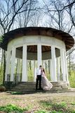 Pregnant couple near a gazebo. A young couple walking in a park near a gazebo stock photography