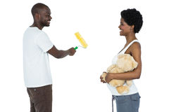 Pregnant couple painting with paint roller Royalty Free Stock Photography