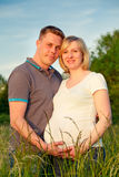 Pregnant couple in the park. Happy pregnant couple in the park Royalty Free Stock Photography