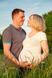 Pregnant couple in the park. Happy pregnant couple in the park Stock Photo