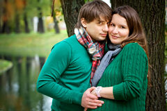 Pregnant couple in  the park. Pregnant couple  wearing green sweaters relaxing in the park Stock Photography
