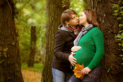 Pregnant couple in  the park. Pregnant couple  wearing green sweaters relaxing in the park Stock Images