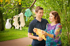 Pregnant couple in park holding baby dress. And smiling Royalty Free Stock Images