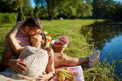 Pregnant couple in the park by the lake in the rays of sunlight. At sunset embrace and kiss Royalty Free Stock Image