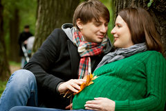 Pregnant couple in  the park. Pregnant couple  wearing green sweaters relaxing in the park Stock Photos