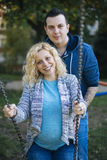 Pregnant couple in the park. Young pregnant couple in the park Royalty Free Stock Image