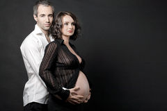 Pregnant couple posing on dark background. Royalty Free Stock Photography