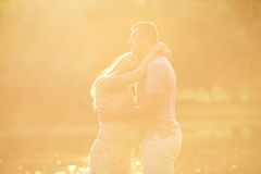 Pregnant couple in the rays of sunlight at sunset. Husband hugs. His pregnant wife tenderly. The concept of a happy family, love and pregnancy Royalty Free Stock Photography