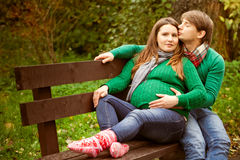 Pregnant couple relaxing on the bench Stock Photos