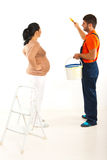 Pregnant couple renovate room. Pregnant women talking with husband in uniform to paint the wall room Royalty Free Stock Photos