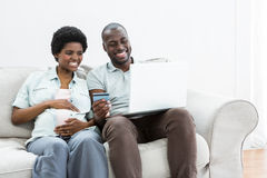 Pregnant couple shopping online on laptop Royalty Free Stock Images