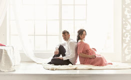 Pregnant couple sitting back to back on floor against big window Stock Image