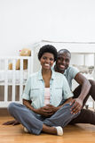 Pregnant couple sitting near baby cradle Royalty Free Stock Images