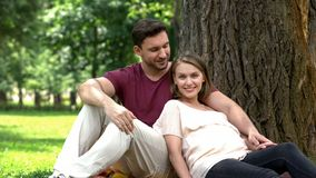 Pregnant couple sitting in park, smiling into camera, happy maternity, parenting royalty free stock images
