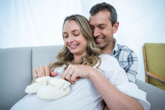 Pregnant couple sitting on sofa Stock Photography