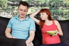 Pregnant couple on sofa Stock Image