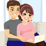 Pregnant Couple Sofa Laptop Stock Photos