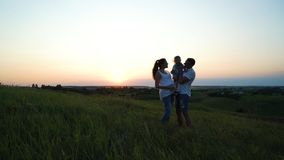 Pregnant couple with toddler daughter have leisure time outdoors at sunset royalty free stock images