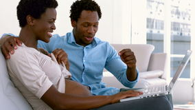Pregnant couple using laptop for video chat. In slow motion stock video footage