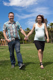 Pregnant couple walking outdoors Stock Images