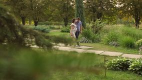 Pregnant couple walking together in Park in summer stock footage