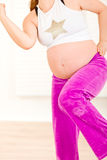 Pregnant doing fitness exercises. Closeup. Royalty Free Stock Image