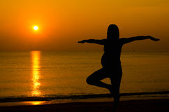 Pregnant doing yoga on the beach. Silhouette of pregnant doing yoga on the beach in morning stock photos