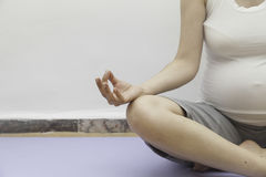 Pregnant doing yoga in lotus position Stock Photo