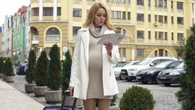 Pregnant elegant lady with suitcase looking for hotel with map, business trip. Stock photo stock photo