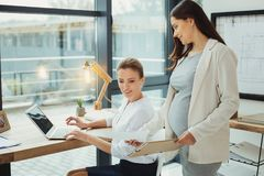 Pregnant employee giving document to her boss before having her maternity leave