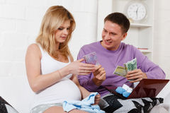 Pregnant family with money. Family budget. Stock Photography