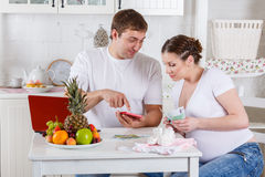 Pregnant family with money. Family budget. Stock Photos