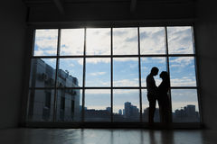 Pregnant family is standing near a window. Pregnant family stands by the window, silhouette against the sky Stock Images