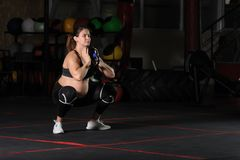 Pregnant female athlete doing goblet squats. With kettlebell in dark gym royalty free stock photos