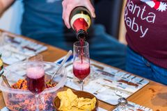 Pregnant female in christmas pullover holding bottle and pouring red non alcoholic wine into champagne glass on table.  Royalty Free Stock Photo