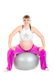 Pregnant female doing exercises on fitness ball Royalty Free Stock Photos