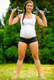Pregnant Female Doing Shoulder Press Exercise With Dumbbells In. Full length portrait of confident pregnant female doing shoulder press exercise with dumbbells stock image