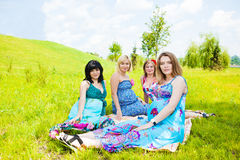 Pregnant female friends. Four pregnant female friends relaxing in park Stock Photos