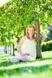 Pregnant female in park. Beautiful pregnant female in park royalty free stock image