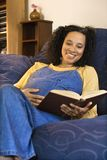 Pregnant female reading. Portrait of pregnant female reading a book and holding her stomach Stock Photos